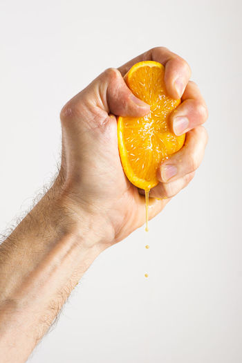 Anonymous Citrus Fruit Crushing Fingers Freshly Squeezed Freshly Squeezed Orange Juice Fruit Half Hand Squeezing Juicing Male Man Man's Hand Orange Orange Juice  Person Squeeze Squeezing Squeezing Oranges Thumb Vertical Visual Feast White Background