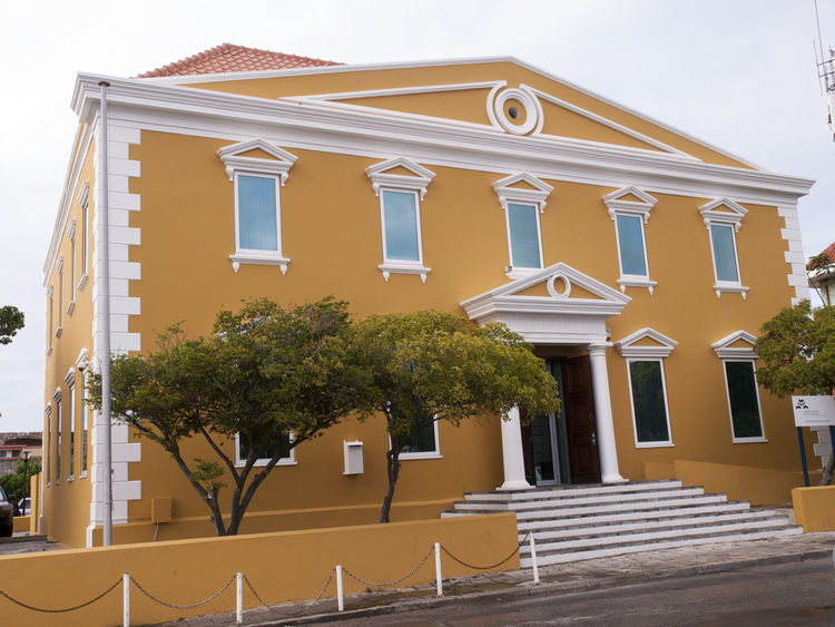 Willemstad,Curaçao is an island country in the southern Caribbean Sea, approximately north of the Venezuelan coast, that is a constituent country of the Kingdom of the Netherlands. Architectural Feature Architecture Building Exterior Built Structure Curacao Curacao (willemstad) Curaçao Town Hall Day Exterior Façade Green Color Growth No People Outdoors Outside Tree Willemstad Window Yellow