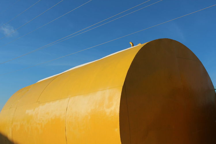 Yellow cylindrical shape against blue sky