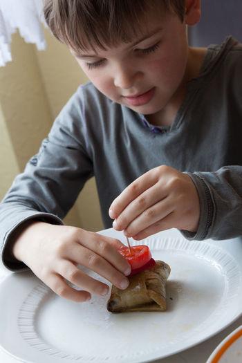 Boy Preparing Beef Kebab In Kitchen