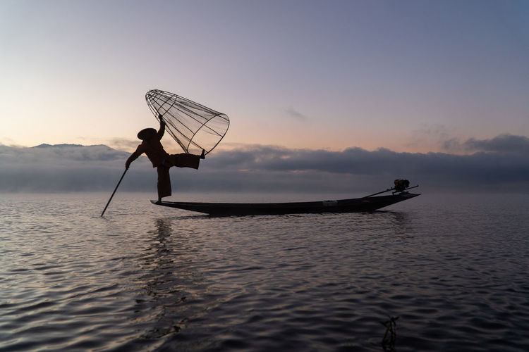 Silhouette of traditional fisherman with boat on inle lake during sunrise against sky