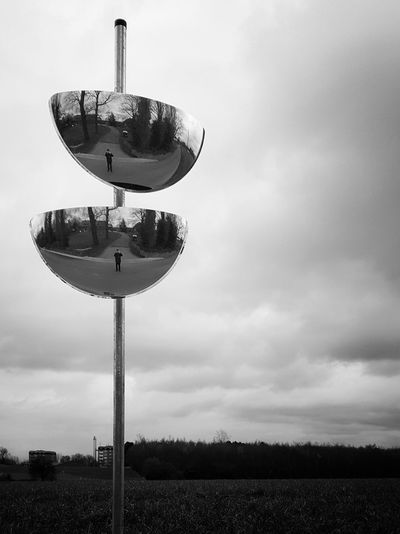 Traffic Mirrors On Field Against Cloudy Sky