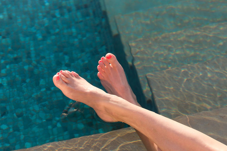 Low section of woman relaxing in swimming pool