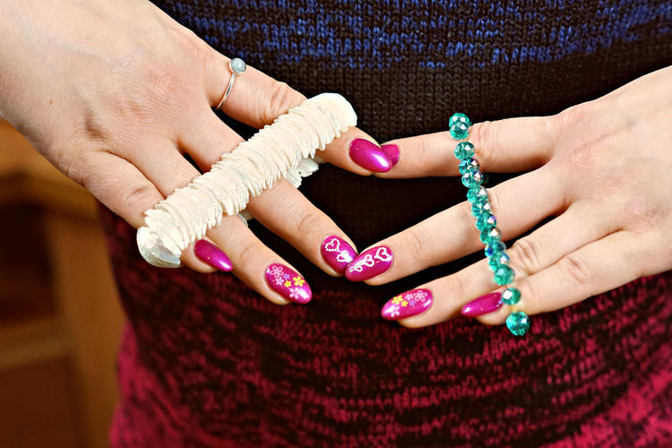 Midsection of woman holding bracelets