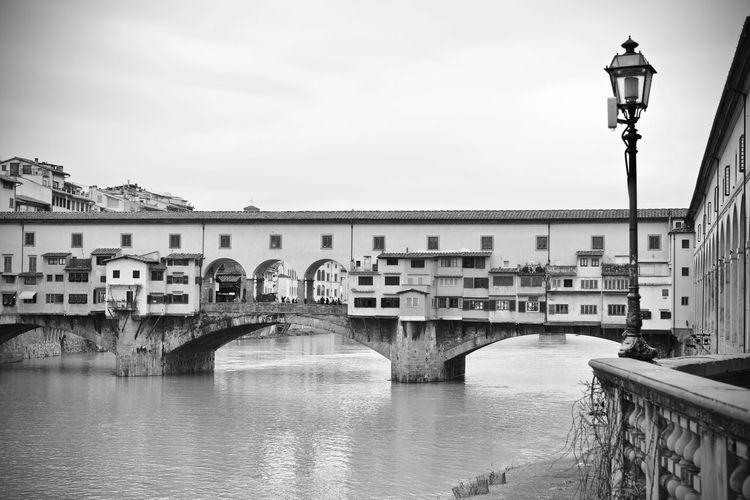 Bridge Over River By Buildings Against Sky