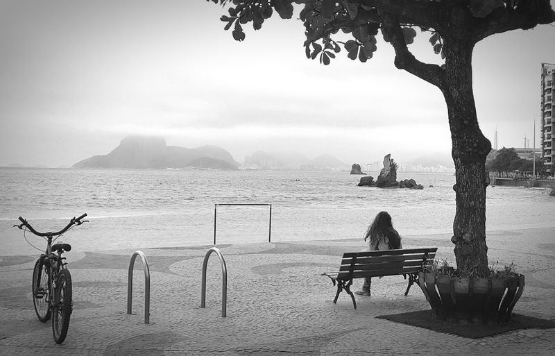 Rear View Of Woman Sitting On Bench At Promenade