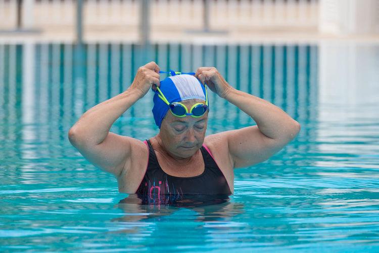 Senior woman wearing swimming goggles in pool