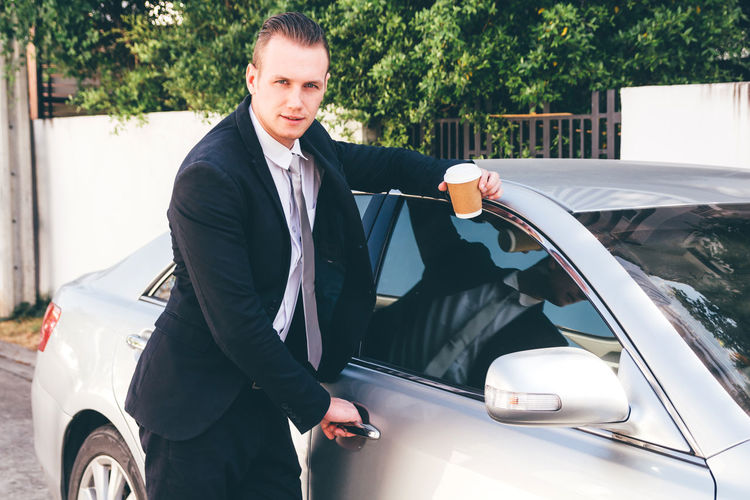 Portrait of businessman opening car door on road