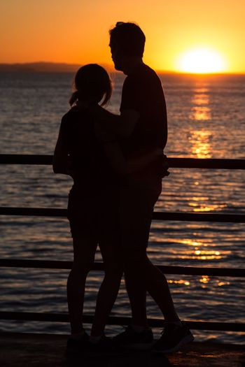 Silhouette man and woman standing on pier by sea against sky during sunset
