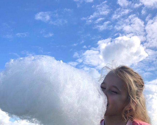 Girl eating cotton candy against sky