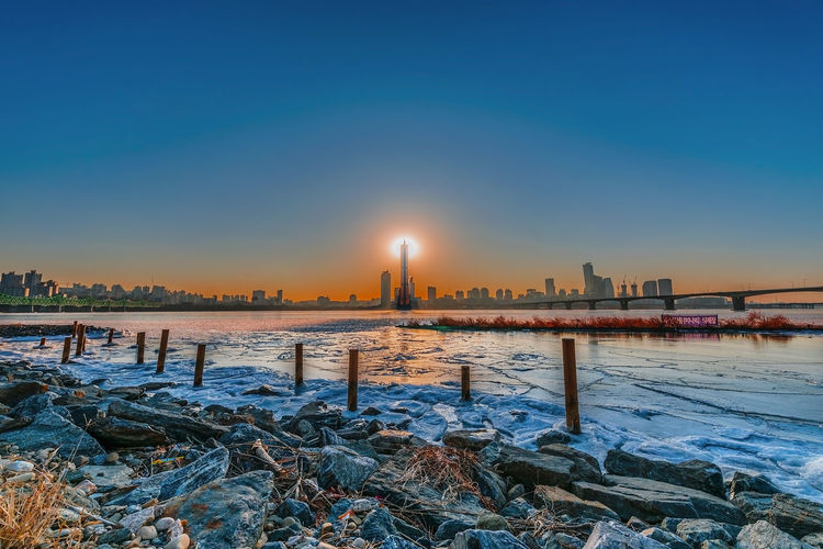 Evening sunset at the Han River in winter South Korea Architecture Building Building Exterior Built Structure City Cityscape Cold Temperature Landscape Nature No People Office Building Exterior Outdoors Scenics - Nature Sky Skyscraper Snow Sun Sunset Tower Travel Destinations Water Winter