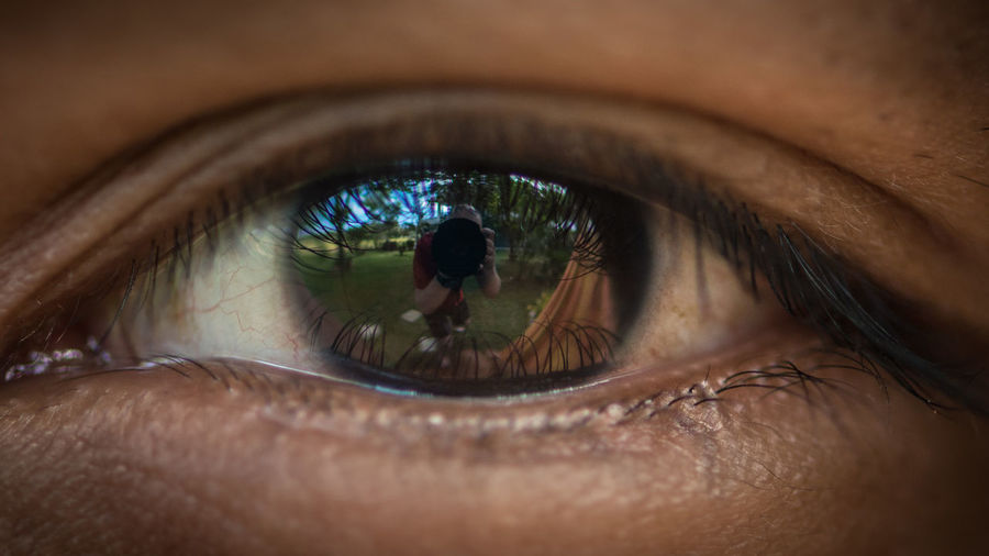 Close-up of person eye with reflection of man photographing with camera