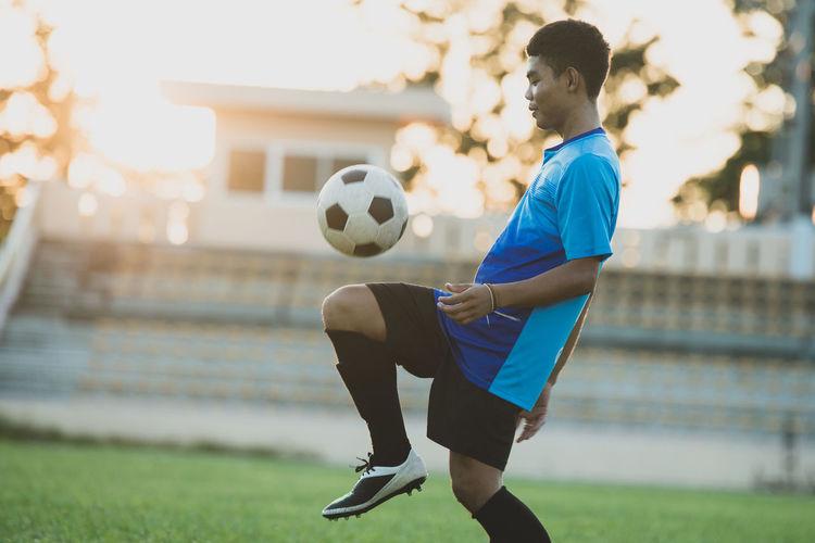 Woman playing soccer ball on grass