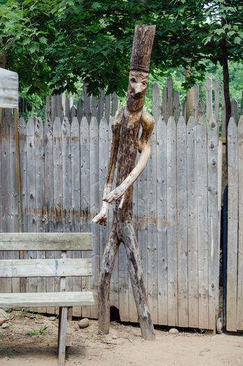 Stick Man sculpture art at an outside festival Stick Man Sculpture Art Logs Branches Wood Wooden Vertical Outdoors Fun Whimsical Playful Face Legs Arms Likeness Artistic Fence Nature Tree Tall Hat Carved Creative Weathered Scary Bench