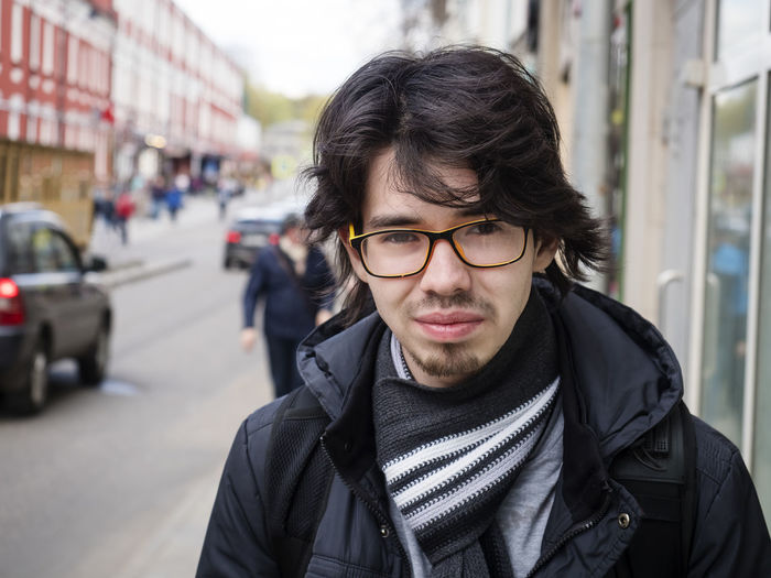 Portrait Young Adult Eyeglasses  Glasses One Person Front View Focus On Foreground Young Men Real People Lifestyles City Clothing Looking At Camera Architecture Headshot Day Jacket Street Warm Clothing Scarf Outdoors Hairstyle