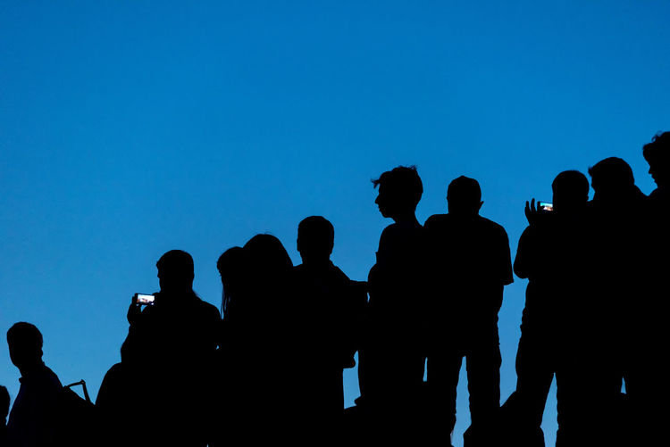 Silhouette people against clear blue sky
