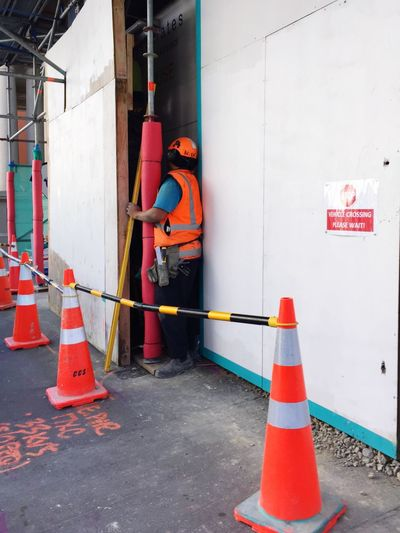 Manual Worker With Traffic Cones At Construction Site