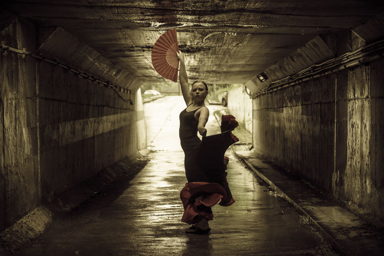 Young woman dancing in tunnel