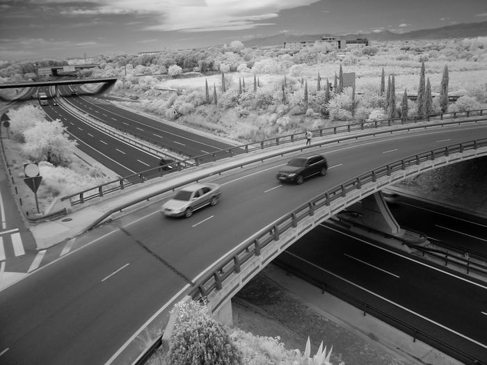 Infrared image of cars on bridge over road against sky