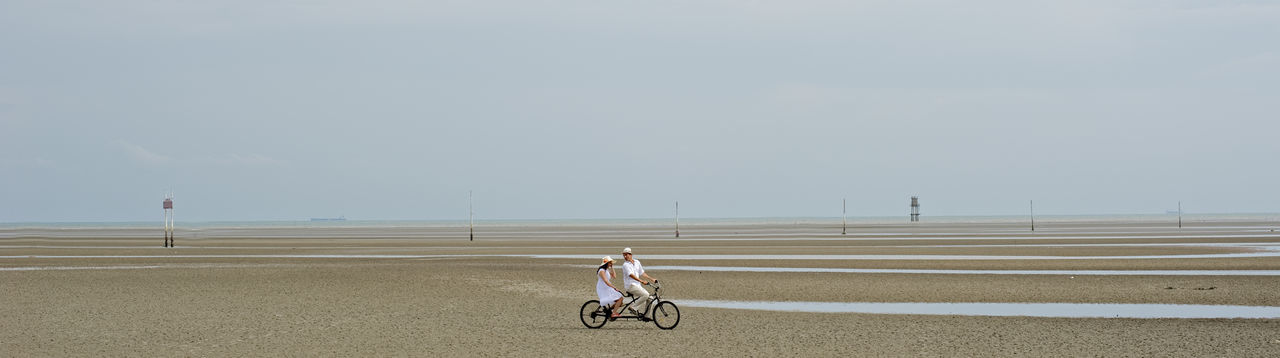 Panoramic view of man with woman riding bicycle at sandy beach against sky