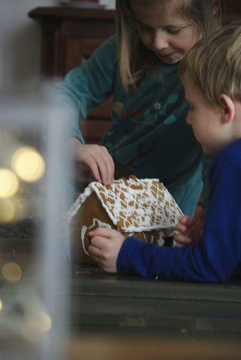 Siblings eating gingerbread house on table