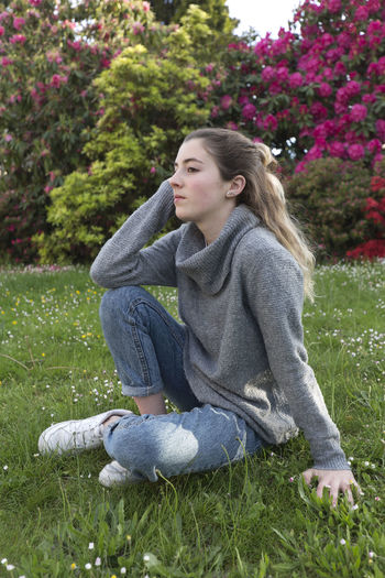 16 year old teenager sitting in a park with grass and flowers, taken in Limoges, France. 16 Years Spanish Woman Adolescent Casual Clothing Contemplation Grass Hairstyle Land Leisure Activity Lifestyles Looking Away One Person Outdoors person Plant Portrait Real People Relaxation Sitting Teen Teenager Teenagers Only Women Young Women