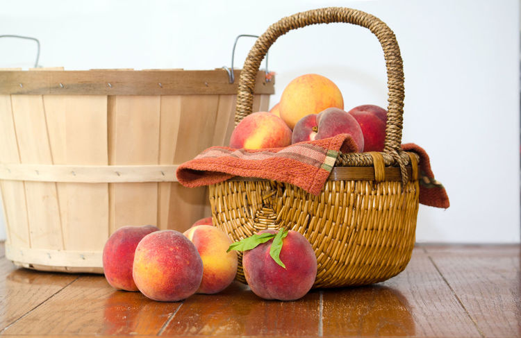 fresh picked peaches with a wicker basket and bushel basket on white Agriculture Fall Colors Freshness Nature USA Basket Container Food Food And Drink Freshness Fruit Healthy Eating Indoors  Juicy Fruit Michigan Peaches Orange Color Organic Peanuts Peach Still Life Table Wellbeing Wood - Material Yellow