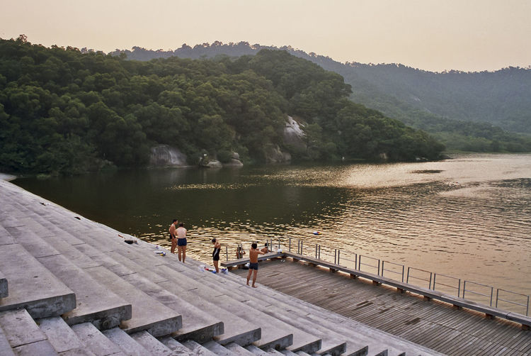 People standing on steps by lake against clear sky