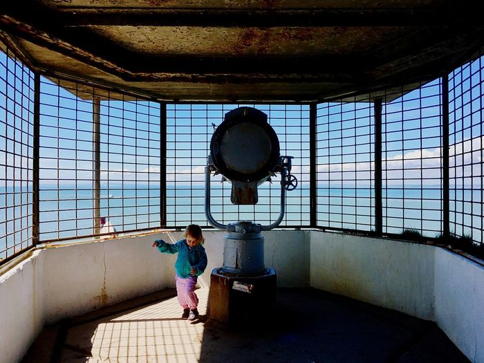 Girl standing in lighthouse on sunny day