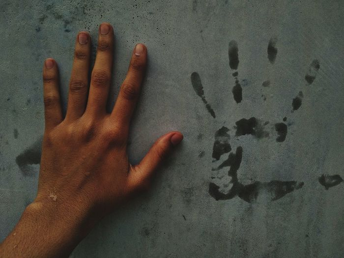 Close-up of hand touching wall