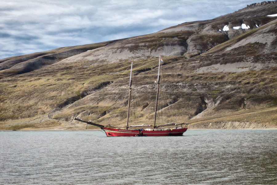 """Noorderlicht"" at the Spitsbergen Coast Beauty In Nature Boat Calm Cliff Cloud - Sky Journey Mast Mode Of Transport Mountain Nature Nautical Vessel Non-urban Scene Outdoors Sailboat Sea Spitsbergen Spitzbergen Tallship Tourism Tranquil Scene Tranquility Transportation Vacations Water Waterfront"