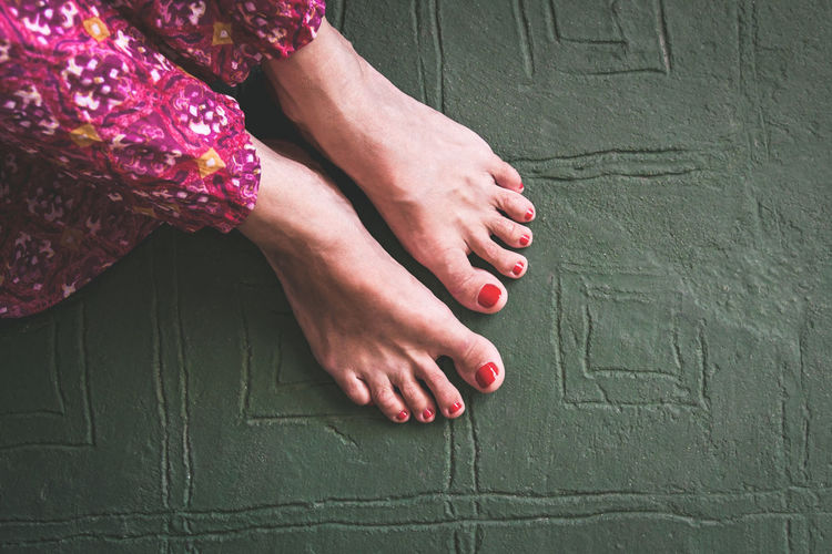 Close up view of barefoot woman with red nails and colorful hippie style skirt. Top view of trendy girl sitting on green vintage decorated floor. Relax, female intimacy, healt and solitude concept. Above Alone Attractive Background Batik Beautiful Beauty Body Care Casual Caucasian Color Comfort Cute Design Easy Feet Finger Foot Fun Green Healthy Holiday Indoors  Interior Lady Legs Leisure Lifestyle Living Modern Nature One Pedicure People person Portrait Pose Posing Pretty Relaxed Resting Room Sit Sitting Spa Travel Vacation Young