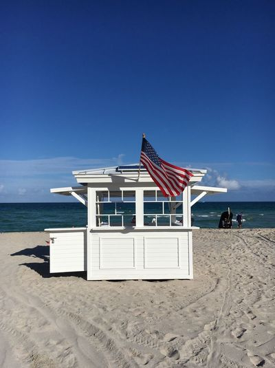American flag waving on lifeguard hut at beach against blue sky