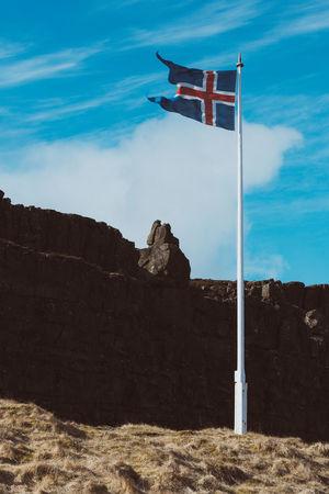 Icelandic flag at the mid-atlantic ridge, thingvellir national park. Beauty In Nature Blue Sky Day Flag Flutter Fluttering Iceland Icelandic Low Angle View Mid-atlantic Ridge Nature No People Outdoors Patriotism Pingvellir Pollen Rocks Sky Þingvallakirkja þingvellir