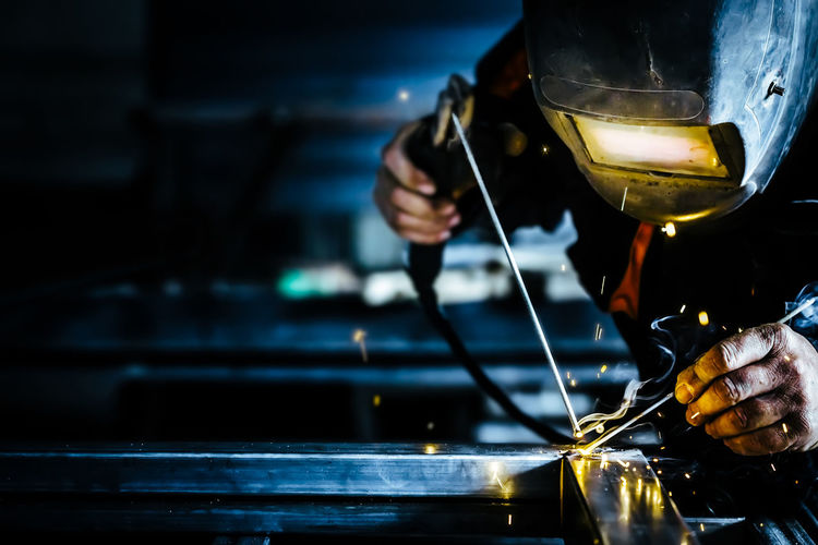 Welder welding metal in factory