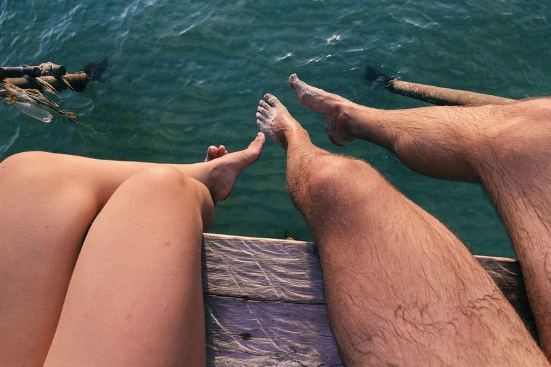 Low section of couple sitting against rippled water