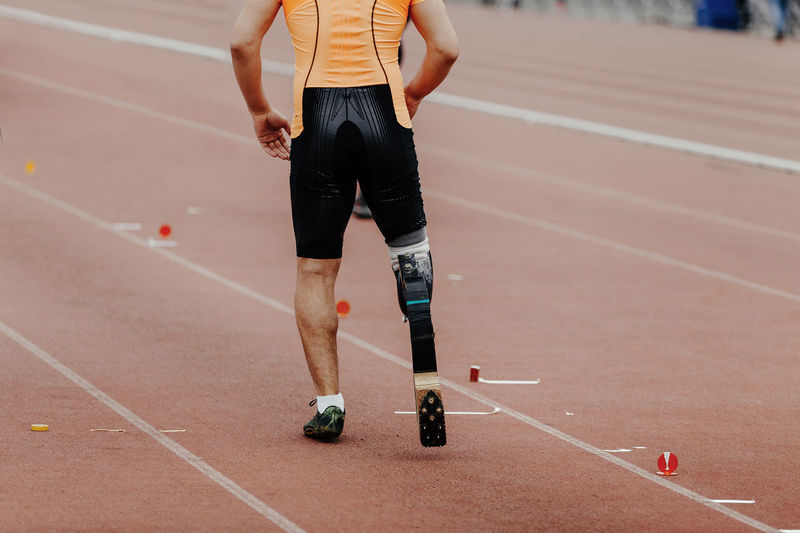 Low section of man with amputated leg running on track