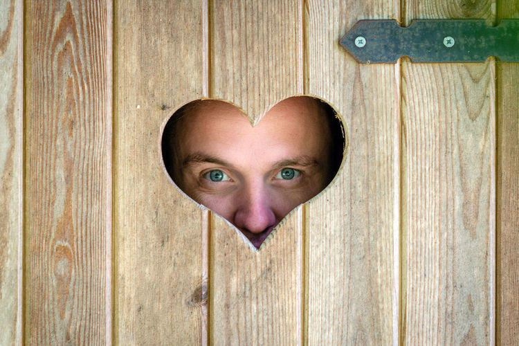Close-up portrait of man peeking through heart shape on wooden door
