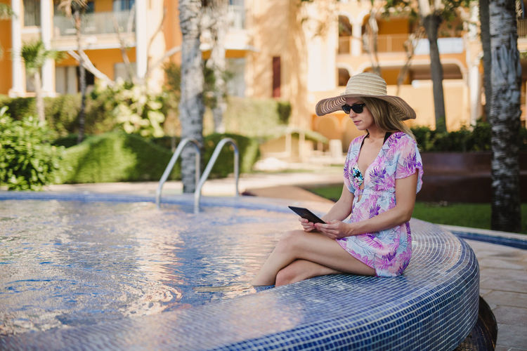 A beautiful woman reading in the pool in a tropical setting. Sitting One Person Real People Leisure Activity Lifestyles Women Technology Hat Wireless Technology Side View Connection Day Casual Clothing Young Adult Clothing Young Women Three Quarter Length Outdoors Hairstyle Ready-to-eat Kindle Pool Hat Sunglasses
