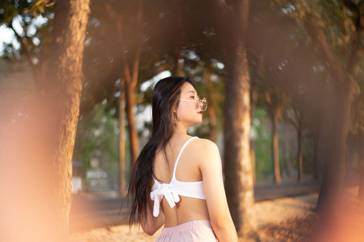 Young woman looking away while standing against tree