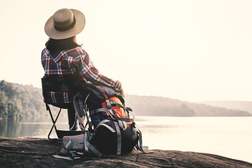Backpack Beauty In Nature Clothing Hat Lifestyles Nature One Person Outdoors Sitting Sky Water