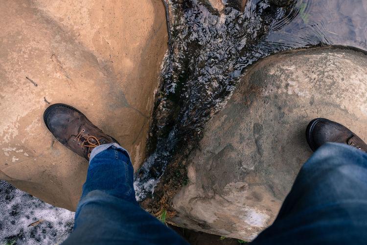 Low Section Of Man Walking On Rock