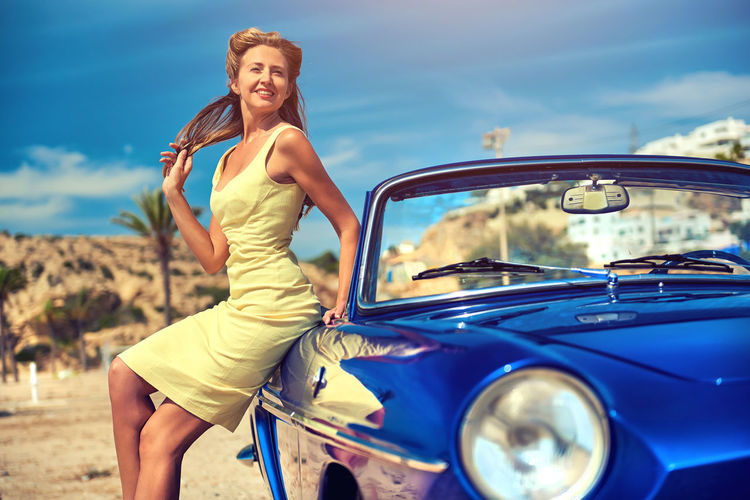 Portrait Of Smiling Young Woman Sitting On Car Against Blue Sky