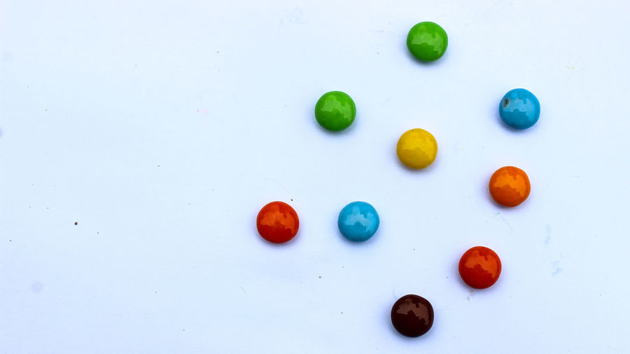 High angle view of multi colored candies against white background