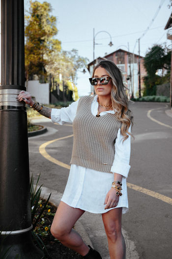 Portrait of young woman wearing sunglasses standing on road in city