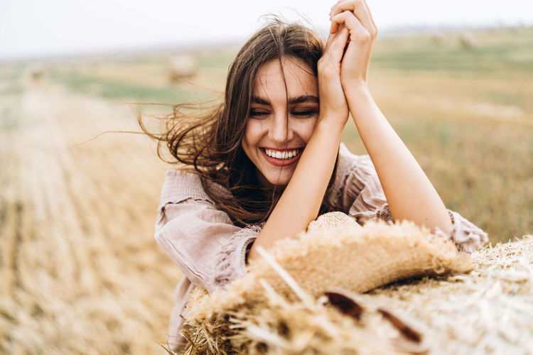 Close-up of smiling young woman with eyes closed by hay bale