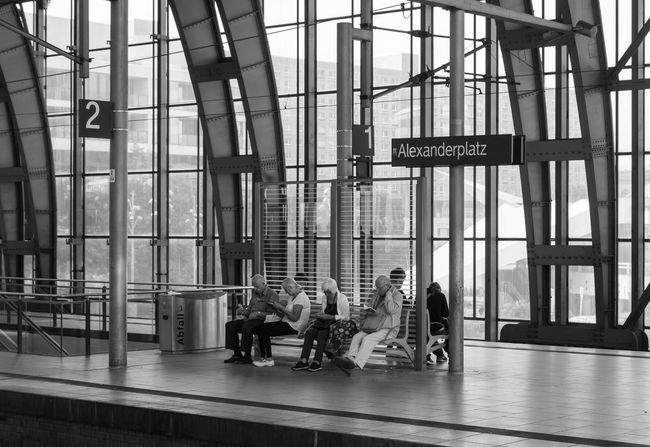 Alexanderplatz B&w Bahnhof Bahnsteig  Black And White City Life Communication Flooring Full Length Indoors  Men Old People Person S-bahnhof Sbahnhof Sitzbank Station Street Photography Streetphoto_bw Text Transportation Building - Type Of Building Waiting Warten