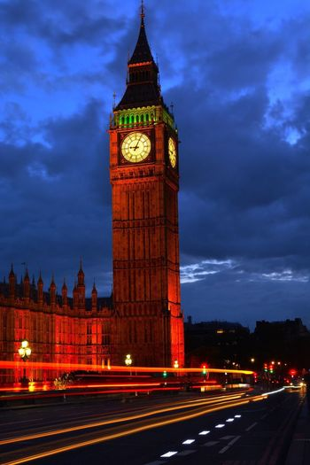 Light trail on street by illuminated big ben against cloudy sky