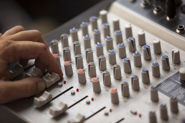 Cropped Hand Of Man Mixing Sound