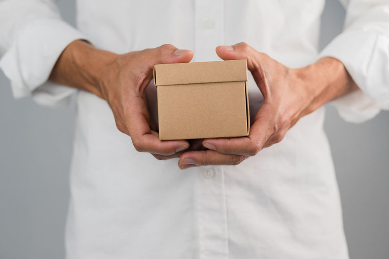 Midsection of man holding mobile phone in box